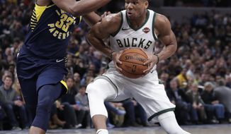 Milwaukee Bucks forward Giannis Antetokounmpo (34) drives on Indiana Pacers center Myles Turner (33) during the second half of an NBA basketball game in Indianapolis, Wednesday, Feb. 13, 2019. The Bucks defeated the Pacers 106-97. (AP Photo/Michael Conroy)