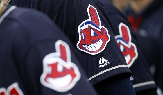 In this June 19, 2017 file photo, members of the Cleveland Indians wear uniforms featuring mascot Chief Wahoo as they stand on the field for the national anthem before a baseball game against the Baltimore Orioles in Baltimore.  (AP Photo/Patrick Semansky, File)  **FILE**
