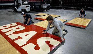 In this Saturday, Feb. 9, 2019 photo, workers install some of the 200 wooden panels that make up the basketball floor for Nebraska's women's NCAA college basketball game at Pinnacle Bank Arena in Lincoln, Neb. By next winter, Husker basketball players will be dribbling on a new court, with a new design and maybe a new logo. Arena officials are seeking bids on a new floor to be delivered in September and in use for next season. (Francis Gardler/Lincoln Journal Star via AP)