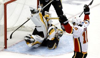 Calgary Flames' Derek Ryan (10) celebrates after teammate Andrew Mangiapane put a shot behind Pittsburgh Penguins goaltender Matt Murray (30) for a goal in the first period of an NHL hockey game in Pittsburgh, Saturday, Feb. 16, 2019. (AP Photo/Gene J. Puskar)