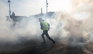 A yellow vest protester runs amid tear gas during scuffles with riot police officers Saturday, Feb.16, 2019 in Paris. Hundreds of yellow vest protesters marched through Paris, one of seven scattered demonstrations in the French capital Saturday, for the 14th straight weekend. (AP Photo/Thibault Camus)
