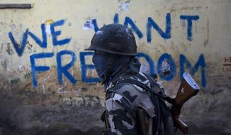 """FILE- In this Aug. 29, 2016 file photo, an Indian paramilitary soldier walks past graffiti on a wall in Srinagar, Indian-controlled Kashmir. As India considers its response to the suicide car bombing of a paramilitary convoy in Kashmir that killed dozens of soldiers on Feb. 14, 2019, a retired military commander who oversaw a much-lauded military strike against neighboring Pakistan in 2016 has urged caution. India blamed the attack on Pakistan and promised a """"crushing response."""" New Delhi accuses its archrival of supporting rebels in Kashmir, a charge that Islamabad denies. (AP Photo/Dar Yasin, File)"""