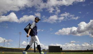 Seattle Mariners' Ichiro Suzuki walks onto a practice field during baseball spring training Saturday, Feb. 16, 2019, in Peoria, Ariz. (AP Photo/Charlie Riedel)