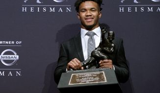 FILE - In this Dec. 8, 2018, file photo, Oklahoma quarterback Kyler Murray holds the Heisman Trophy after winning the award in New York. Before picking football over baseball, Kyler Murray got some advice from another famous two-sport star. Tim Tebow says he told Murray to follow his heart when deciding between the Oakland Athletics and pursuing an NFL career.  (AP Photo/Craig Ruttle, File)