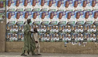 "A child leads a blind man as they walk past a wall of campaign posters in Kano, in northern Nigeria, Saturday, Feb. 16, 2019. A civic group monitoring Nigeria's now-delayed election says the last-minute decision to postpone the vote a week until Feb. 23 ""has created needless tension and confusion in the country."" (AP Photo/Ben Curtis)"