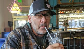 In this undated photograph, Dave Query, owner of Centro Mexican Kitchen, sips water through a straw in his restaurant in Boulder, Colo. Colorado restaurateurs such as Query want to see one law to guide them regarding the dispensing of straws to customers instead of a myriad of local rules and, as a result, are working with state lawmakers to come up with a regulation. (Sam Brasch/Colorado Public Radio via AP)