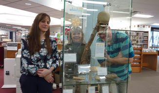 "This Thursday Jan. 17, 2019 photo shows Ohio County Public Library staff members, from left, Erin Rothenbuehler, Dottie Thomas and Sean Duffy examine a new exhibit, ""Wheeling in 250 Objects,"" at the library in Wheeling W.Va.. The major exhibit coincides with Wheeling 250, a year-long celebration of the 250th anniversary of the city's founding. (Linda Cumins/The Intelligencer via AP)"