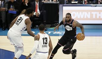 Team LeBron's LeBron James, of the Cleveland Cavaliers works against Team Giannis' Paul George, of the Oklahoma City Thunder, and Team Giannis' Joel Embiid, of the Philadelphia 76ers, during the second half of an NBA All-Star basketball game, Sunday, Feb. 17, 2019, in Charlotte, N.C. The Team LeBron won 178-164. (AP Photo/Gerry Broome)