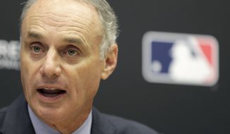 FILE - In this Nov. 27, 2018 file photo Baseball Commissioner Rob Manfred speaks during a news conference at MLB headquarters in New York. Pitch clocks are coming for spring training games. Looking to speed the pace of play in baseball, Manfred said, Sunday, Feb. 17, 2019, pitchers will have 20 seconds to deliver to the plate when teams play exhibition games in Arizona and Florida beginning this week. (AP Photo/Seth Wenig, file) **FILE**