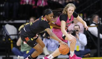 Maryland guard Kaila Charles, left, fights for the ball with Iowa guard Kathleen Doyle during the first half of an NCAA college basketball game, Sunday, Feb. 17, 2019, in Iowa City, Iowa. (AP Photo/Charlie Neibergall) **FILE**