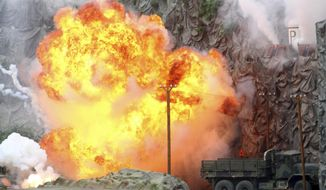 """An explosion strikes during a military demonstration targeting a theatrical """"ballistic missile launchpad"""" at the International Defense Exhibition and Conference in Abu Dhabi, United Arab Emirates, Sunday, Feb. 17, 2019. The biennial arms show in Abu Dhabi comes as the United Arab Emirates faces increasing criticism for its role in the yearlong war in Yemen. (AP Photo/Jon Gambrell)"""