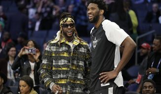 Team Giannis' Joel Embiid, of the Philadelphia 76ers, speaks with Rapper 2 Chainz ahead of the first half of an NBA All-Star basketball game, Sunday, Feb. 17, 2019, in Charlotte, N.C. (AP Photo/Chuck Burton)