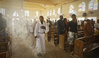 An altar boy swings the thurible of incense during a morning service at the Saint Charles Catholic Church, the site of a 2014 bomb attack blamed on Islamic extremist group Boko Haram, in the predominantly-Christian neighborhood of Sabon Gari in Kano, northern Nigeria Sunday, Feb. 17, 2019. With the leading contenders both northern Muslims, Nigeria's presidential contest has been largely free of the religious pressures that marked the 2015 vote, but the Christian vote is bound to be decisive in a race that could sweep the incumbent out of power. (AP Photo/Ben Curtis)