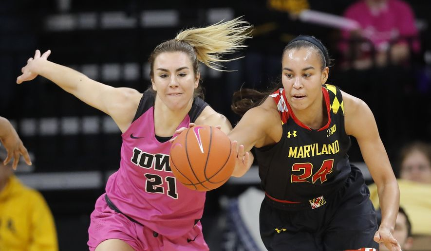 Maryland forward Stephanie Jones, right, fights for the ball with Iowa forward Hannah Stewart, left, during the first half of an NCAA college basketball game, Sunday, Feb. 17, 2019, in Iowa City, Iowa. (AP Photo/Charlie Neibergall)