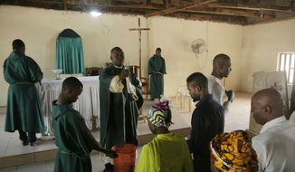 Rev. Father Maurice Kwairanga, center, blesses parishioner during a Mass at St. Charles Catholic Church, in Ngurore, Nigeria, Sunday, Feb. 17, 2019. (AP Photo/ Sunday Alamba) **FILE**