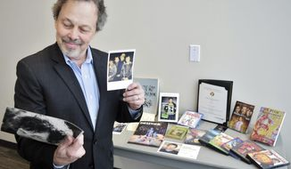In this Thursday, Feb. 7, 2019, Curtis Armstrong, an actor, producer and writer, holds some of the 30-years of memorabilia from his career in film and television at Oakland University in Rochester, Mich. Armstrong, an alumnus of the university, has donated the material to Oakland University's archives. (Natalie Broda/The Oakland Press via AP)