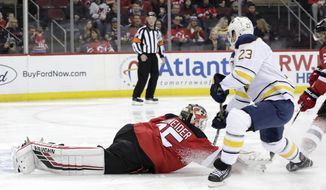 New Jersey Devils goaltender Cory Schneider (35) dives forward to deflect the puck as Buffalo Sabres center Sam Reinhart (23) attacks during the first period of an NHL hockey game, Sunday, Feb. 17, 2019, in Newark, N.J. (AP Photo/Julio Cortez)