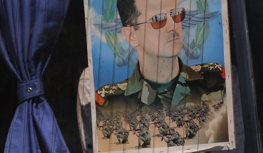 FILE - In this Aug. 13, 2018 file photo, a Syrian refugee holds a poster of President Bashar Assad in a bus window at the border crossing point of Jdedeh Yabous, on his way to Syria. Assad said Sunday, Feb. 17, 2019, that only the Syrian army can protect groups in northern Syria. In a speech in the Syrian capital Damascus on Sunday, he appeared to be referring to U.S.-allied Kurdish groups, which fear a Turkish assault once American troops withdraw from northeastern Syria. (AP Photo/Sergei Grits, File)