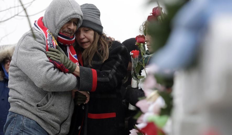 People attend at a makeshift memorial Sunday, Feb. 17, 2019, in Aurora, Ill., near Henry Pratt Co. manufacturing company where several were killed on Friday. Authorities say an initial background check five years ago failed to flag an out-of-state felony conviction that would have prevented a man from buying the gun he used in the mass shooting in Aurora. (AP Photo/Nam Y. Huh)