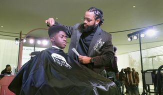 """In this Sunday, Feb. 17, 2019 file photo, Timaun Norris, 15, gets a haircut from Corvette Derden during """"The Art of the Cut"""" event at Toledo Museum of Art's GlasSalon in Toledo, Ohio. (Jetta Fraser/The Blade via AP) ** FILE **"""