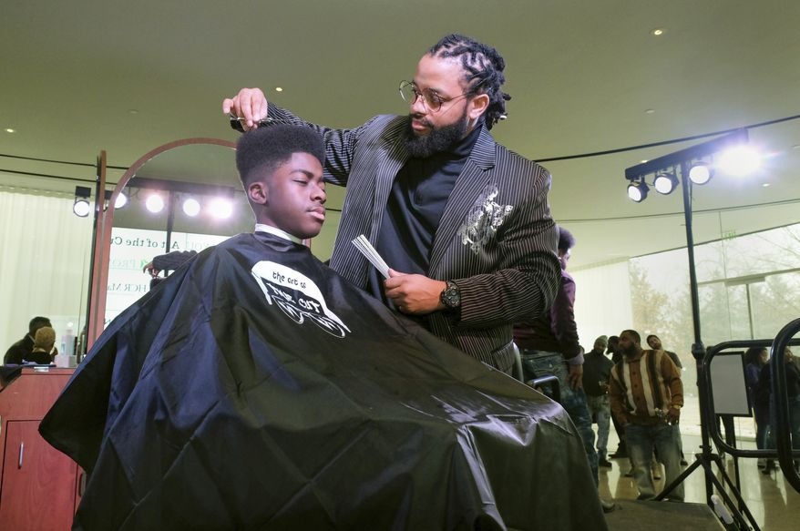 "In this Sunday, Feb. 17, 2019 file photo, Timaun Norris, 15, gets a haircut from Corvette Derden during ""The Art of the Cut"" event at Toledo Museum of Art's GlasSalon in Toledo, Ohio. (Jetta Fraser/The Blade via AP) ** FILE **"
