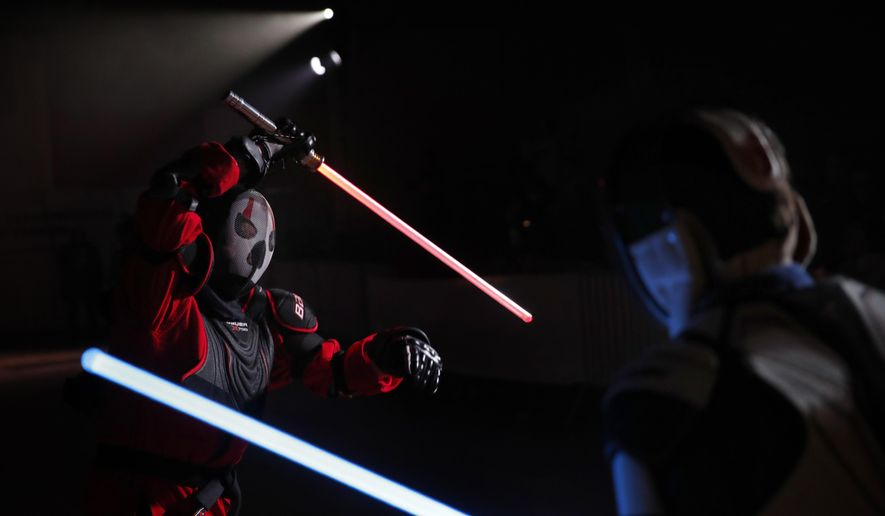 """In this Sunday, Feb. 10, 2019, photo, Julien Esprit, left, competes with Jean Baptiste Marchetti-Waternaux during a national lightsaber tournament in Beaumont-sur-Oise, north of Paris. In France, it is easier than ever now to act out """"Star Wars"""" fantasies. The fencing federation has officially recognized lightsaber dueling as a competitive sport. (AP Photo/Christophe Ena)"""