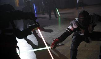 "In this Sunday, Feb. 10, 2019, photo, competitors battle during a national lightsaber tournament in Beaumont-sur-Oise, north of Paris. ""We wanted it to be safe, we wanted it to be umpired and, most of all, we wanted it to produce something visual that looks like the movies, because that is what people expect,"" said Michel Ortiz, the tournament organizer. (AP Photo/Christophe Ena) ** FILE **"
