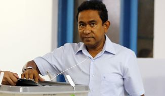 FILE - In this Sept. 23, 2018, file photo, Maldivian President Yameen Abdul Gayoom, right, casts his vote at a polling station during presidential election day in Male, Maldives. A Maldives court ordered the arrest and detention of former Maldives President Yameen Abdul Gayoom on Monday for alleged money laundering.. (AP Photo/Eranga Jayawardena, File)