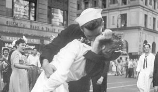 In this Aug. 14, 1945, file photo provided by the U.S. Navy, a sailor and a woman kiss in New York's Times Square, as people celebrate the end of World War II. The ecstatic sailor shown kissing a woman in Times Square celebrating the end of World War II has died. George Mendonsa was 95. It was years after the photo was taken that Mendonsa and Greta Zimmer Friedman, a dental assistant in a nurse's uniform, were confirmed to be the couple. (Victor Jorgensen/U.S. Navy, File)