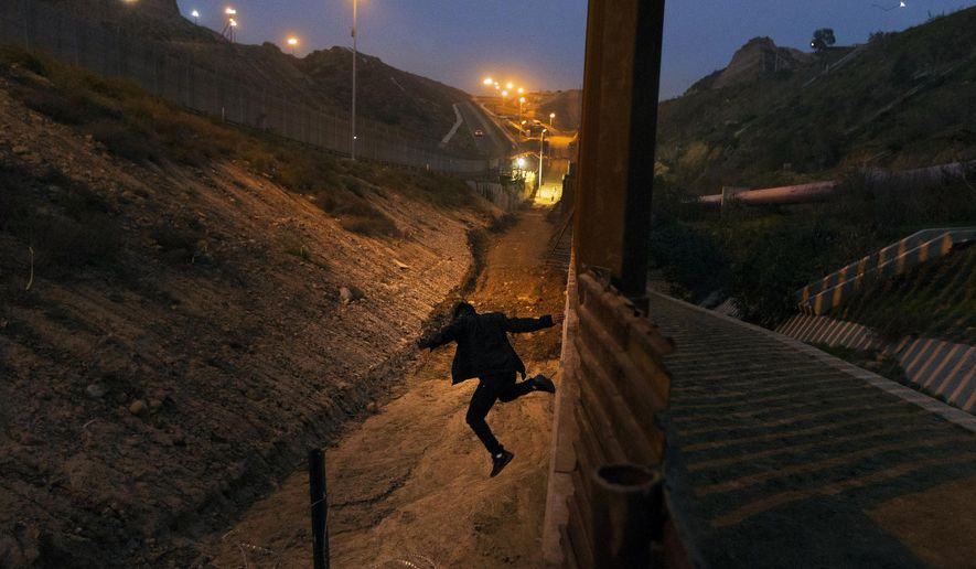 In this Dec. 21, 2018, file photo, a Honduran youth jumps from the U.S. border fence in Tijuana, Mexico.   California's attorney general filed a lawsuit Monday, Feb. 18, 2019, against President Donald Trump's emergency declaration to fund a wall on the U.S.-Mexico border. Xavier Becerra released a statement Monday saying 16 states — including California — allege the Trump administration's action violates the Constitution. (AP Photo/Daniel Ochoa de Olza, File)