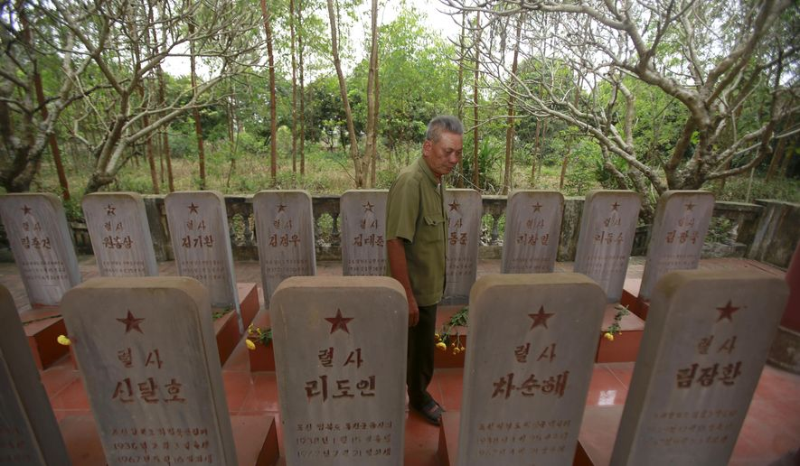 In this Feb. 16, 2019, photo, war veteran Duong Van Dau walks in between a row of headstones at a memorial for North Korean fallen pilots in Bac Giang province, Vietnam. The fourteen headstones of the pilots who died while fighting American bombers alongside the Vietnamese army during the Vietnam war remain as a symbol of Vietnam-North Korea friendship. (AP Photo/Hau Dinh)