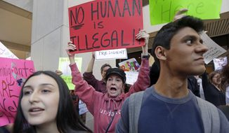 Protester Joan Wynne, center, chants anti-Trump and anti-Gimenez slogans in downtown Miami. Tuesday, Jan. 31, 2017. Miami-Dade County Mayor Carlos Gimenez issued a controversial order last week assuring the Trump administration that Miami-Dade is not functioning as a sanctuary city for illegal immigrants. (AP Photo/Alan Diaz)