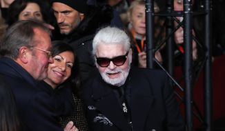 Fashion designer Karl Lagerfeld arrives for the Champs Elysee Avenue illumination ceremony for the Christmas season, in Paris, Thursday, Nov. 22, 2018. Chanel's iconic couturier, Karl Lagerfeld, whose accomplished designs as well as trademark white ponytail, high starched collars and dark enigmatic glasses dominated high fashion for the past 50 years, has died Tuesday Feb.19, 2019. He was around 85 years old. (AP Photo/Christophe Ena)