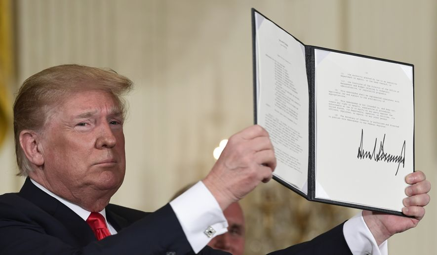 In this June 18, 2018, photo, President Donald Trump holds up the space policy directive that he signed during a National Space Council meeting in the East Room of the White House in Washington.  Trump is moving closer toward his goal of creating a Space Force, but it won't begin as a separate military branch as the president envisioned. The Space Force instead initially will be created as part of the Air Force, but could be spun into a separate military department in the future. That's according to senior administration officials who briefed journalists on a directive Trump is scheduled to sign Tuesday to establish the Space Force. (AP Photo/Susan Walsh) **FILE**