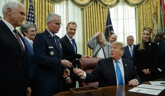 """President Donald Trump hands a pen to Air Force Gen. Paul Selva after signing """"Space Policy Directive 4"""" in the Oval Office of the White House, Tuesday, Feb. 19, 2019, in Washington. (AP Photo/ Evan Vucci) **FILE**"""