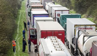 FILE - In this April 6, 2016 file photo, truck drivers stand among trucks on the highway from Brussels to Luxembourg, in Spontin, Belgium. The European Union has reached a tentative agreement on the first specific EU standards for trucks to get polluting CO2 levels down. A Tuesday, Feb. 19, 2019, agreement between negotiators from the European Parliament and member states says that such emissions will have to be 30 percent down by 2030 compared to today's levels. (AP Photo/Geert Vanden Wijngaert, File)