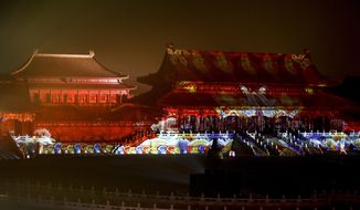 In this Tuesday, Feb. 19, 2019, photo, a firefighter walks by the Forbidden City projected with colourful lights for the Lantern Festival in Beijing. China lit up the Forbidden City on Tuesday night, marking the end of 15 days of lunar new year celebrations. It was not a Lantern Festival the last emperor, who abdicated in 1912, would have recognized. There were lanterns, but those lucky enough to snag tickets saw a laser light show and historic buildings bathed in colorful lights. Others watched from outside the vast walled compound in Beijing, from where Ming and Qing dynasty emperors ruled for five centuries. (AP Photo/Andy Wong)