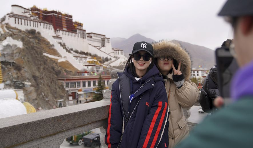 In this Feb. 9, 2019, photo released by Xinhua News Agency, tourists pose for souvenir photos in front of the Potala Palace in Lhasa, southwest China's Tibet Autonomous Region. China is barring foreign travelers from Tibet over a period of several weeks that includes a pair of sensitive political anniversaries. Travel agencies contacted Wednesday, Feb. 20 said foreign tourists would not be allowed into the Himalayan region until April 1. (Jigme Dorje/Xinhua via AP)