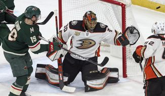 Minnesota Wild's Luke Kunin, left, shoots wide of Anaheim Ducks goalie Ryan Miller in the second period of an NHL hockey game Tuesday, Feb.19, 2019, in St. Paul, Minn. (AP Photo/Jim Mone)