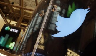 In this Nov. 6, 2013, file photo, the Twitter bird logo is on an updated phone post on the floor of the New York Stock Exchange. (AP Photo/Richard Drew, FILE)