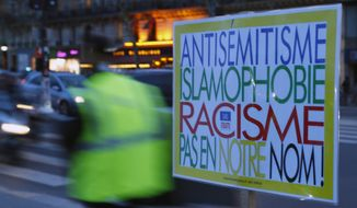 "A poster reading ""Anti-Semitism, Islamophobia, Racism, Not in Our Name"" during a gathering decrying anti-Semitism at Place de la Republique in Paris, Monday, Feb. 18, 2019 amid an upsurge in anti-Semitism in France. It reached a climax last weekend with a torrent of hate speech directed at a distinguished philosopher during a march of yellow vest protesters, adding to questions about the radicalized fringes of the movement hidden within French society and troubling the nation. (AP Photo/Francois Mori)"