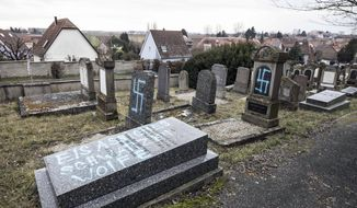 Vandalized tombs with tagged swastikas are pictured in the Jewish cemetery of Quatzenheim, eastern France, Tuesday, Feb.19, 2019. Marches and gatherings against anti-Semitism are taking place across France following a series of anti-Semitic acts that shocked the country. (AP Photo/Jean-Francois Badias)