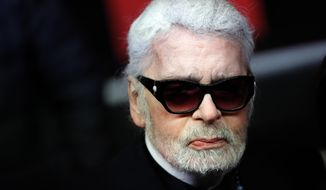 In this Thursday, Nov. 22, 2018, file photo, Fashion designer Karl Lagerfeld poses during the Champs Elysee Avenue illumination ceremony for the Christmas season, in Paris. Chanel says Tuesday, Feb. 19, 2019, its iconic couturier Karl Lagerfeld has died. (AP Photo/Christophe Ena, File)