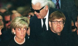 FILE - In this Tuesday, July 22, 1997 file photo, Diana, Princess of Wales, German fashion designer Karl Lagerfeld and British pop-star Elton John, attend the memorial mass for Gianni Versace, inside Milan's gothic cathedral, Italy. Chanel's iconic couturier, Karl Lagerfeld, whose accomplished designs as well as trademark white ponytail, high starched collars and dark enigmatic glasses dominated high fashion for the last 50 years, has died. He was around 85 years old. (AP Photo/Luca Bruno, File)