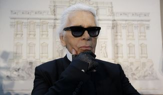 FILE - In this Monday, Jan. 28, 2013 file photo, Karl Lagerfeld poses for photographers prior to the start of a press conference, in Rome. Chanel's iconic couturier, Karl Lagerfeld, whose accomplished designs as well as trademark white ponytail, high starched collars and dark enigmatic glasses dominated high fashion for the last 50 years, has died. He was around 85 years old. (AP Photo/Gregorio Borgia, File)