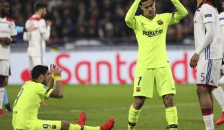 Barcelona forward Luis Suarez, left, and Barcelona forward Philippe Coutinho, right, react during the Champions League round of 16 first leg soccer match between Lyon and FC Barcelona in Decines, near Lyon, central France, Tuesday, Feb. 19, 2019. (AP Photo/Laurent Cipriani)
