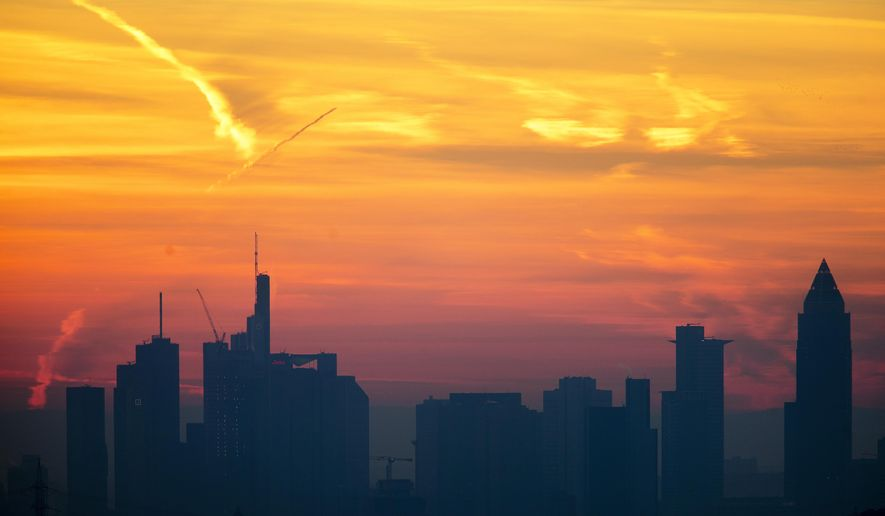 A plane flies over the banking district during sunrise in Frankfurt, Germany, Saturday, Feb. 16, 2019. (AP Photo/Michael Probst)
