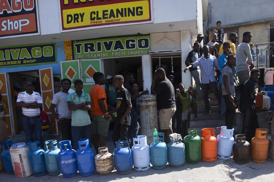 Residents line up to buy propane gas in Port-au-Prince, Haiti, Monday, Feb. 18, 2019. Businesses and government offices slowly reopened across Haiti on Monday after more than a week of violent demonstrations over prices that have doubled for food, gas and other basic goods in recent weeks and allegations of government corruption. (AP Photo/Dieu Nalio Chery)