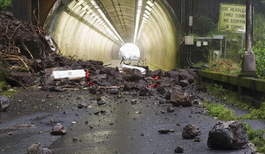 Rocks and debris from a landslide that hit a vehicle are shown on the Pali Highway in Honolulu, Tuesday, Feb. 19, 2019. State transportation officials were assessing the unstable slope above the busy highway after the landslide sent three people to the hospital on Monday. The highway, which connects Honolulu and the east side of Oahu over a steep mountain range, was completely closed and portions will remain shut down all week after multiple landslides in the area. (Craig T. Kojima/Honolulu Star-Advertiser via AP)