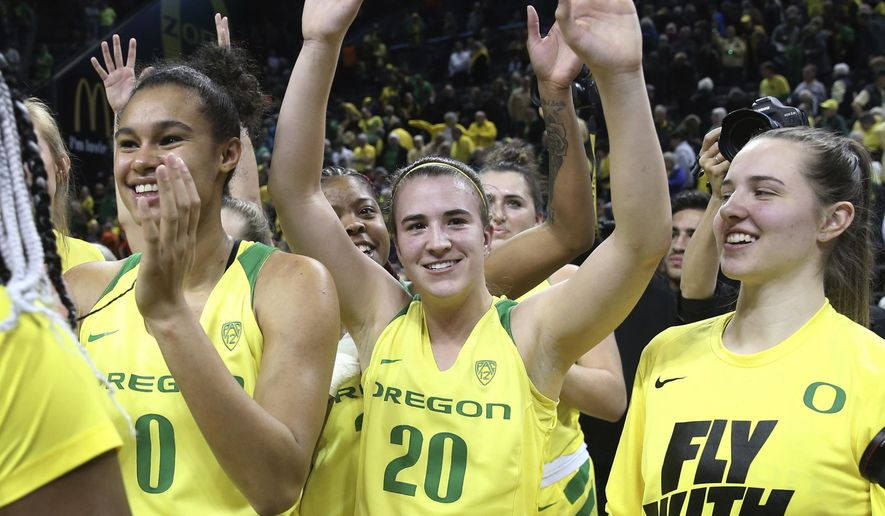 Oregon's Satou Sabally, left, Sabrina Ionescu and Morgan Yeager acknowledge fans after Oregon defeated Oregon State 77-68 in an NCAA college basketball game Friday, Feb. 15, 2019, in Eugene, Ore. (AP Photo/Chris Pietsch)